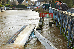 © Licensed to London News Pictures.  22/11/2012. OXFORD, UK. Walkers look at a sunken boat pushed up against a weir near Osney Lock on the River Thames. Strong currents following heavy rain caused the boat to break its moorings. Photo credit :  Cliff Hide/LNP