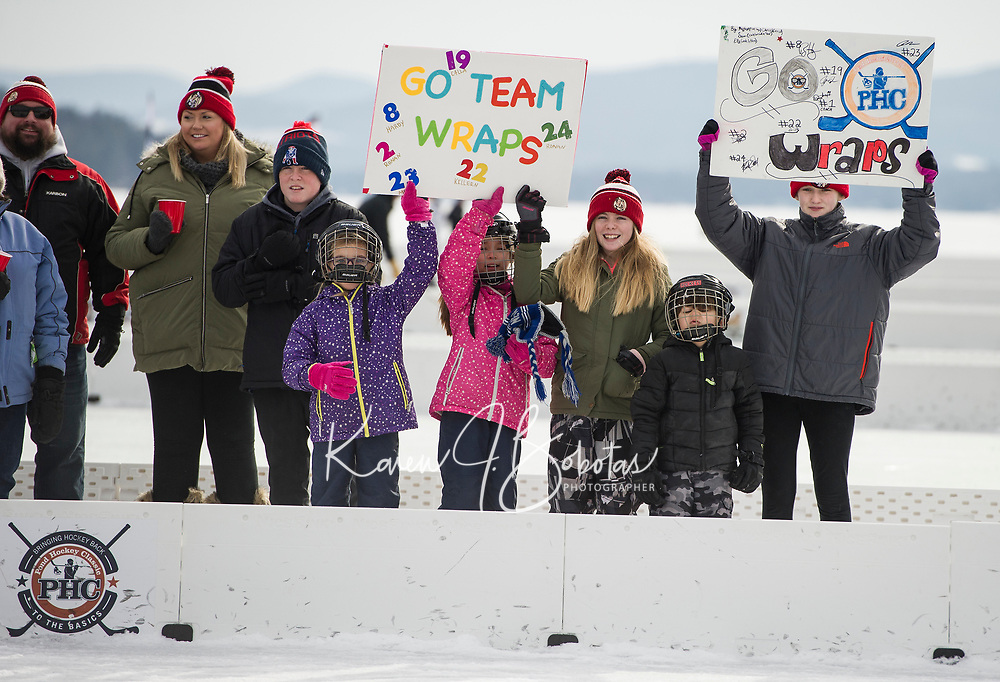 Morgan Hardy, Samantha Hardy, Ella Gilligan and Megan Donnolly hold up signs in support for their team Wrap Solutions from Reading, MA during the quarterfinal round of the 30+ division at the New England Pond Hockey Classic on Sunday.  (Karen Bobotas/for the Laconia Daily Sun)