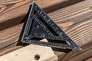 Carpentry measure, plan and design tools on raw wood background. triangular ruler and angle measuring