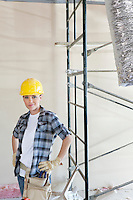 Portrait of mid adult woman standing with hands on hips at construction site
