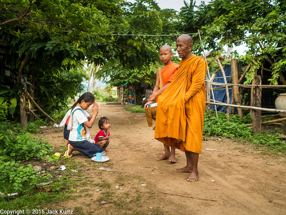 "20 JUNE 2016 - DON KHONE, CHAMPASAK, LAOS:  Girls pray after presenting alms to monks from Wat Khone Nua on their morning alms' rounds, called the ""tak bat"" in Don Khone village on Don Khone Island. Don Khone Island, one of the larger islands in the 4,000 Islands chain on the Mekong River in southern Laos. The island has become a backpacker hot spot, there are lots of guest houses and small restaurants on the north end of the island.    PHOTO BY JACK KURTZ"