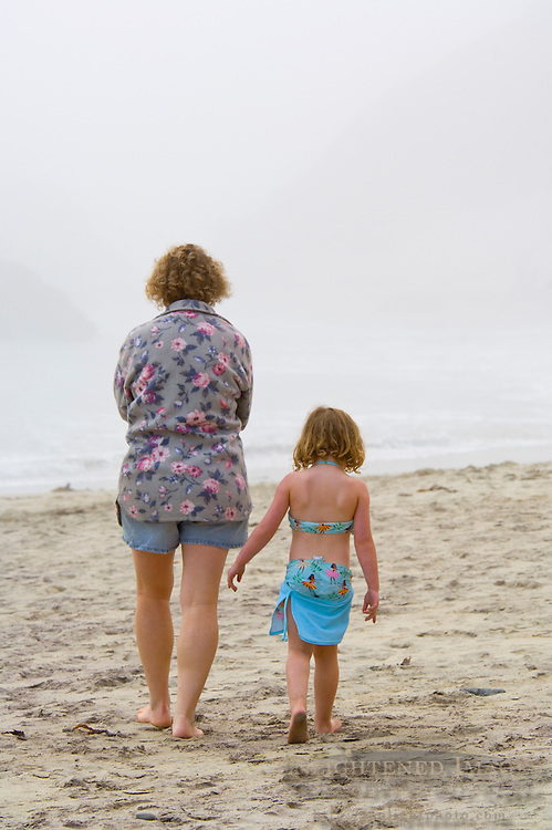 Mother and young daughter walking together on sand in fog at Pfeiffer Beach, Big Sur Coast, Monterey County, California