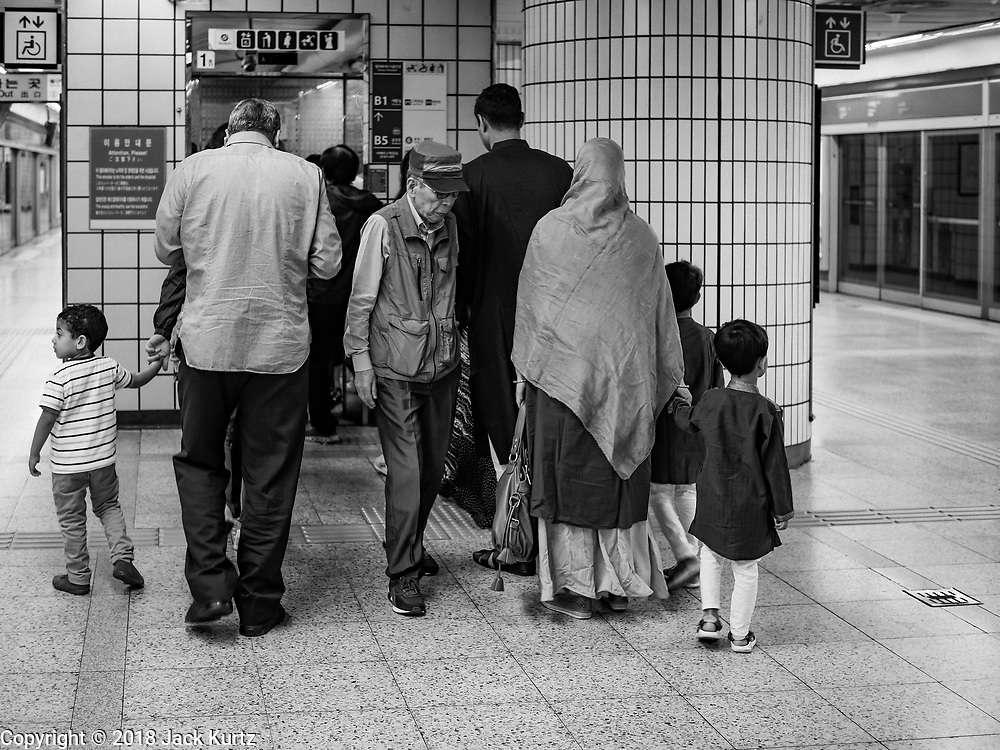 15 JUNE 2018 - SEOUL, SOUTH KOREA:  A Muslim family waits to get an elevator in Itaewon Subway Station on their way to Seoul Central Mosque on Eid al Fitr, the Muslim Holy Day that marks the end of the Holy Month of Ramadan. There are fewer than 100,000 Korean Muslims, but there is a large community of Muslim immigrants in South Korea, most in Seoul. Thousands of people attend Eid services at Seoul Central Mosque, the largest mosque in South Korea.   PHOTO BY JACK KURTZ
