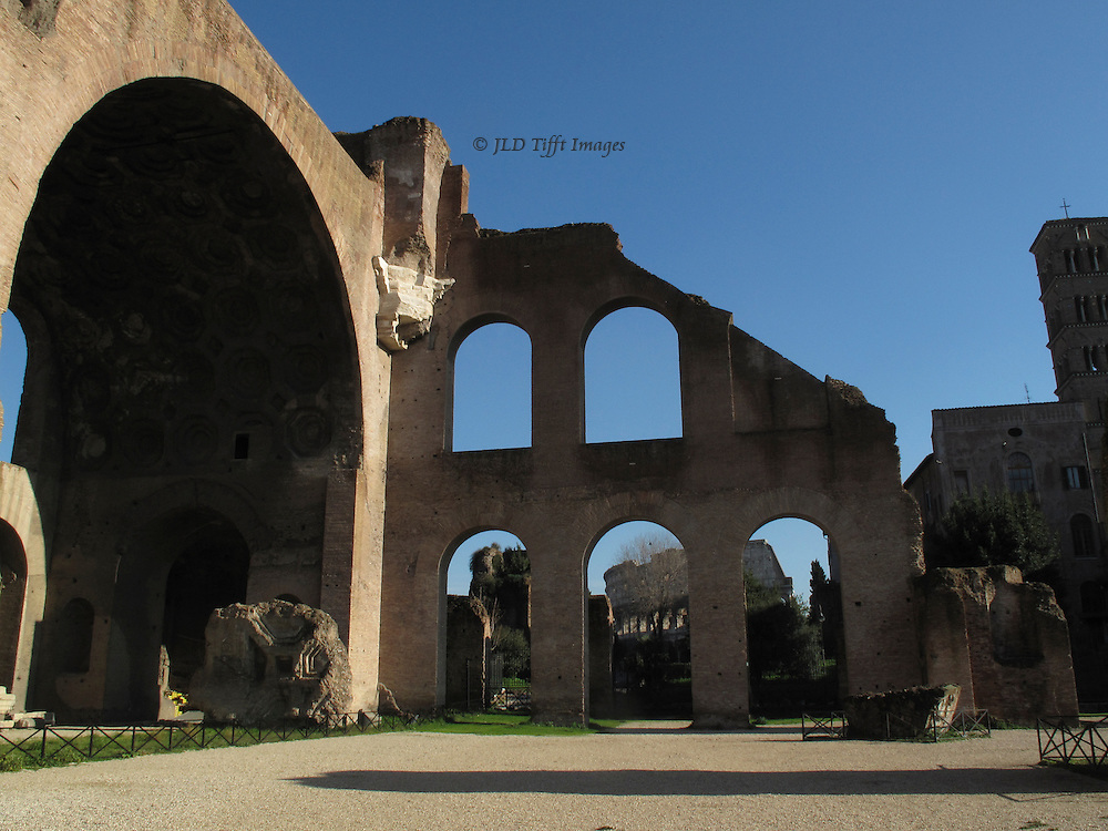 Rome, Basilica of Constantine (begun by Maxentius).  Colosseum visible beyond through the arched openings; one of the vast arches of the main hall on the left of the image.