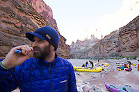 Young man brushing teeth while on a raft trip down the Grand Canyon. Grand Canyon National Park, AZ.