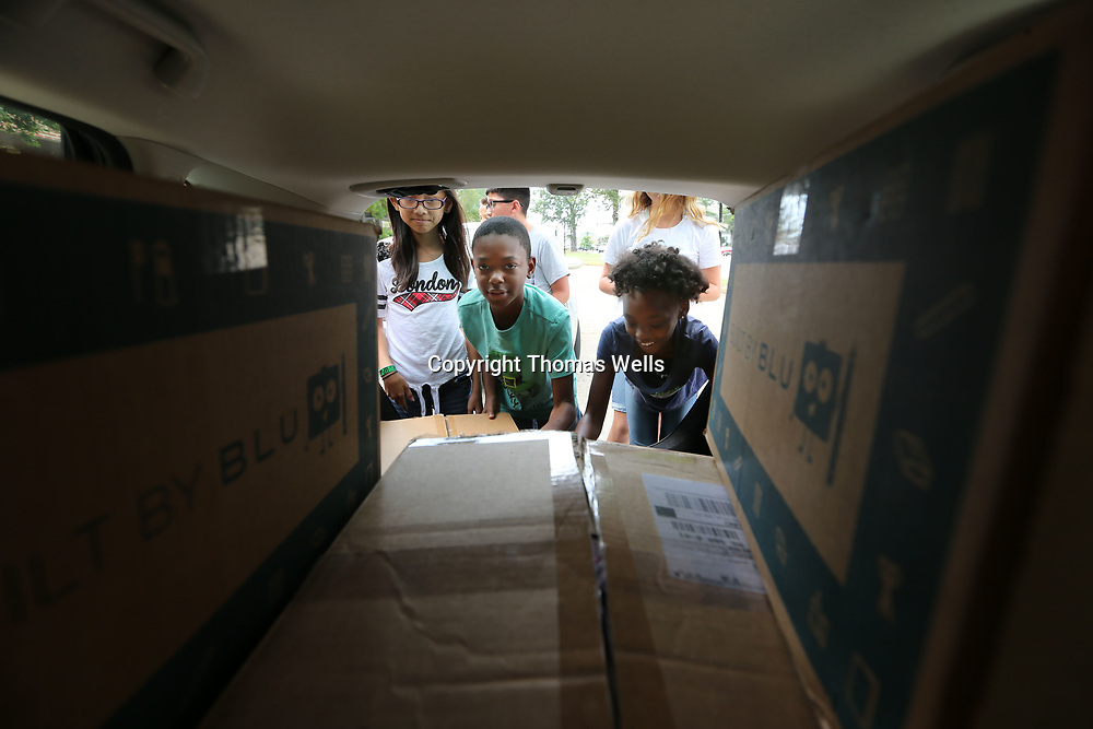 Ethan Taylor, 11, center, and his classmates help unload a car full of backpacks at Milam Elementary School. The backpacks are full of school supplies and will be given out to children in need.