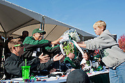 An unidentified boy hands President McDavis flowers during the homecoming parade. Photo by: Ross Brinkerhoff..