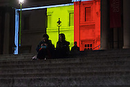 Two women chat on the steps of Trafalgar Square, as the National Gallery and other London landmarks are illuminated in the colours of the Belgian flag in a display of solidarity with Belgium following the terror attacks on March 22nd. Westminster, London<br /> Picture by Paul Davey/Focus Images Ltd +447966 016296<br /> 23/03/2016