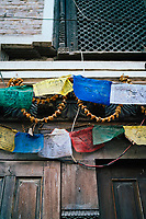 Garlands of dried flowers and prayer flags in a doorway in Patan, Nepal.