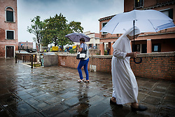 A nun uses an umbrella to shelter from a shower of rain as she walks through Dosoduro, Venice, Italy.<br />