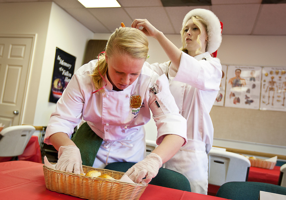 Murray High School ProStart student Kenzie Pollei arranges rolls as her classmate Tristan Thomas fixes her hair during a holiday buffet luncheon at Fire Station 81 in Murray, Wednesday, Dec. 19, 2012. ProStart is a national program for students to learn culinary and management skills in anticipation of working the restaurant business or attending culinary school.