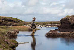 © Licensed to London News Pictures. 13/08/2016. Swinithwaite, UK. A man walks through water with shotgun in hand during a grouse shoot high on the Yorkshire moors in Swinithwaite, North Yorkshire. Yesterday was the glorious 12, the day that traditionally marks the start of the grouse shooting season. Photo credit : Ian Hinchliffe/LNP