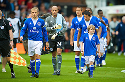 LONDON, ENGLAND - Sunday, September 13, 2009: Everton's captain Phil Neville leads his team out with a mascot to face Fulham during the Premiership match at Craven Cottage. (Photo by David Rawcliffe/Propaganda)