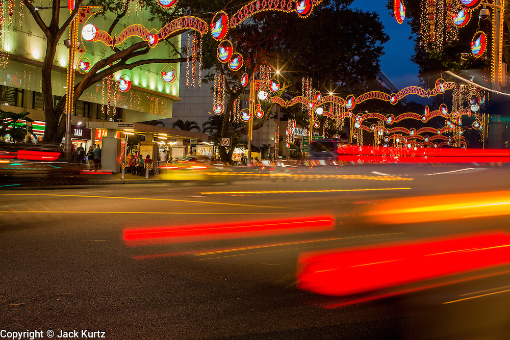 "22 DECEMBER 2012 - SINGAPORE, SINGAPORE:  Traffic goes under Christmas lights on Orchard Road during ""Christmas on a Great Street"" in Singapore. Businesses on Orchard Road, Singapore's famed shopping street, sponsors the annual event. The street is decorated with holiday lights, stores stay open late and crowds pack the area. This is the 8th year Singapore has held the ""Christmas on a Great Street"" event.   PHOTO BY JACK KURTZ"