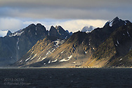 Mountains tower over the sea in Smeerenburgfjorden on the north coast of Spitsbergen island; Svalbard, Norway.
