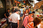 09 JULY 2011 - BANGKOK, THAILAND: People walk through an alley in a market in the Chinatown section of Bangkok, Thailand. Chinatown is the entrepreneurial hub of Bangkok, with thousands of family owned businesses selling wholesale merchandise in everything from food like rice, peanuts and meats, to dry goods like toys and shoes.  PHOTO BY JACK KURTZ
