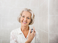 Portrait of happy senior woman spraying perfume in bathroom