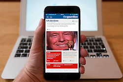 Detail of iPhone smart phone showing online mobile  newspaper front-page headline from The Guardian following Donald Trump's victory in 2016 US Presidential Election