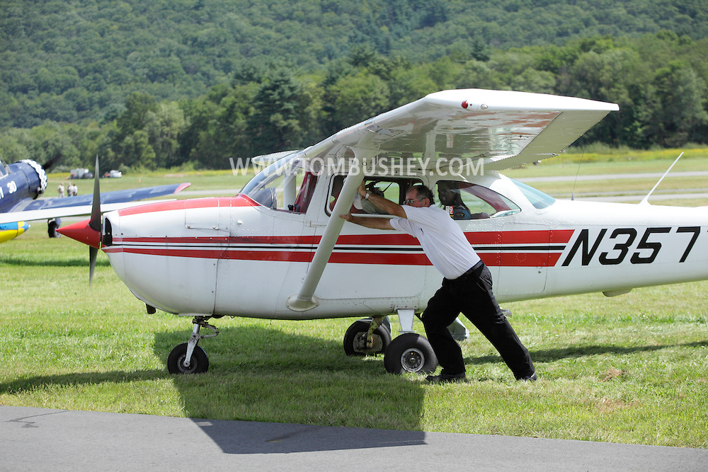 Wurtsboro, NY - A man pushes a single-engine plane from the grass onto the runway at Wurtsboro Airport on Aug. 30, 2009.