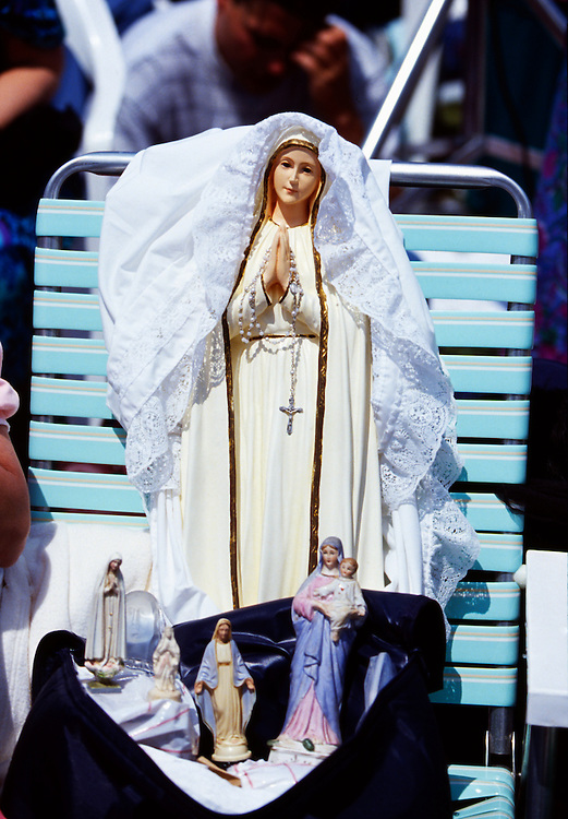 Statues of The Virgin Mary on a plastic lawnchair. <br />
