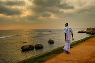 A Sinhalese man walking by the sea on one of the fortified wall of Galle, Sri Lanka