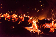 Sparks fly from burning log at night. This was a dead ponderosa pine snag that was ignited by the Cajete Fire and then fell, continuing to burn on the ground. © 2017 David A. Ponton