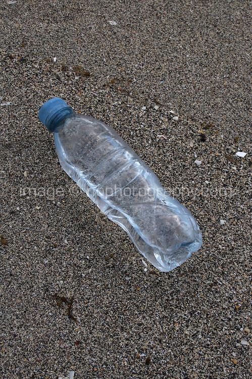 Bottle of water on sandy beach