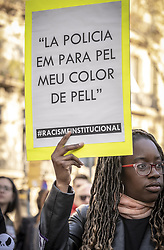 March 23, 2019 - Barcelona, Catalonia, Spain - A black woman is seen holding a placard saying The police stop me for my colour during the demonstration..Thousands of people have marched in Barcelona against fascism and racism. Supported by some 200 social organizations, trade unions and parties, framed in the International Day against Racism, the protest has been focused mainly against the new party of the Spanish right wing VOX already with parliamentary representation. (Credit Image: © Paco Freire/SOPA Images via ZUMA Wire)