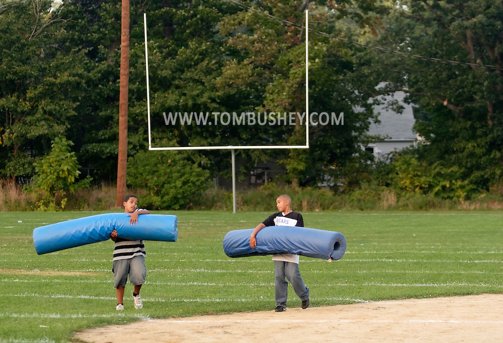 Middletown, NY - Two boys carry protective cushions from the goal posts off the field after an Orange County Youth Football League game between Middletown and Goshen at Watts Park in Middletown on Sept. 22, 2007.