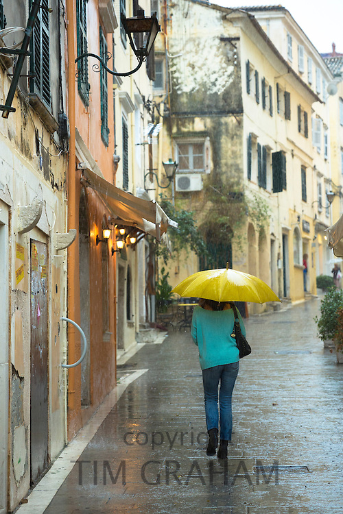 Person walking with umbrella in rainy day scene in Kerkyra, Corfu Town, Greece