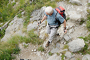 elderly man walking over rocks