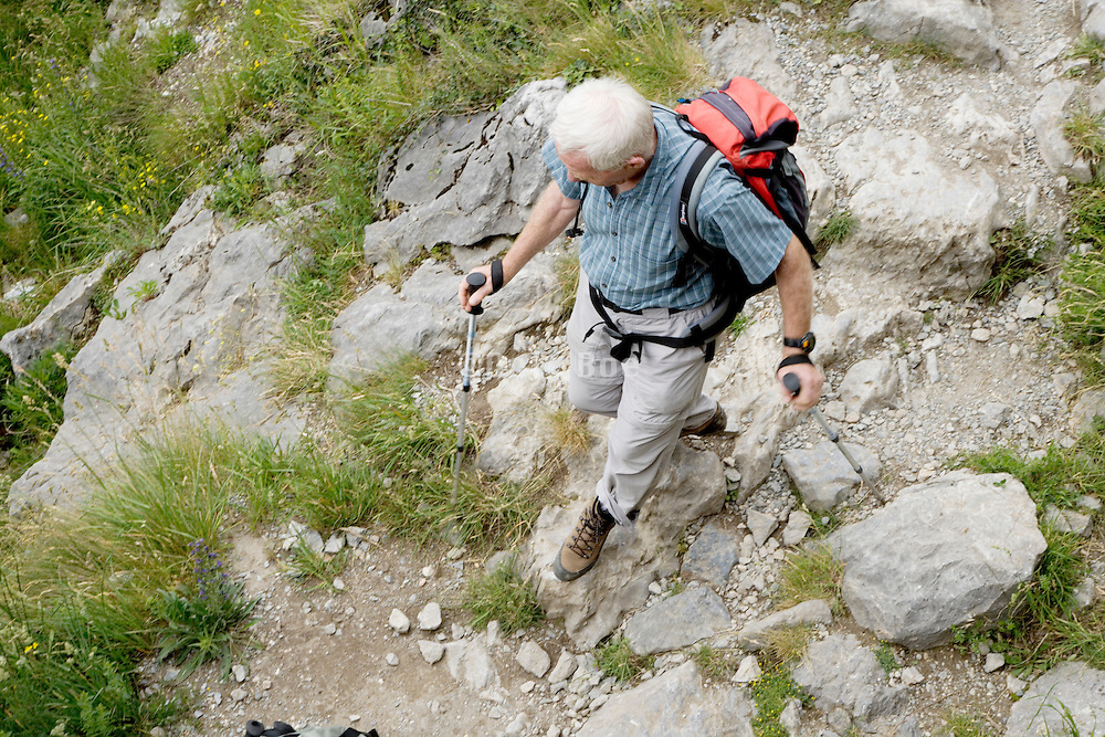 elderly man walking over rocks
