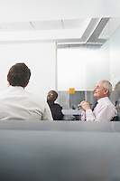 Three businessmen sitting in office side view