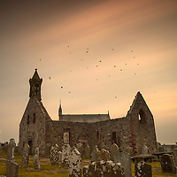 Pitsligo Kirk<br /> <br /> The sky was dark when I arrived. It began to break above my head and what a brilliant thing to happen in a graveyard waiting for the shot.<br /> A swallow flew above and would dive and swoop over the old kirk. I was thinking about sailors and their tattoos of swallows. Swallows mate for life and are very loyal. Like star ships they swirled above the missing roof of the old kirk.<br /> In Christian tradition swallows are considered symbolic of life, death, eternal love and rebirth and so they were part of this nature, which connected with me for this site: a kirk, a graveyard, an old building and a new building.<br /> <br /> Pitsligo Kirk, Rosehearty, Aberdeenshire Damian Shields 2014<br /> Images &copy; Scottish Civic Trust, shown courtesy of Damian Shields Client: Scottish Civic Trust