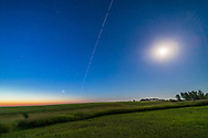 The International Space Station in a dawn pass, as it flies away to the east after passing overhead. This was the morning of July 15, 2017. <br /> <br /> Venus is the bright object at lower left; the overexposed waning Moon is at right. The Pleiades is above Venus, the Hyades cluster is just to the right of Venus. Capella is the bright star at far left. <br /> <br /> This is a composite stack of 24 exposures for the ISS, masked onto a single background image of the sky taken just before the ISS entered the frame. This kept the stars as points rather than trails, while the ISS trailed across the sky. The gaps are from the 2 second interval between 10-second exposures. All with the Canon 6D and 14mm Rokinon lens at f/2.5.