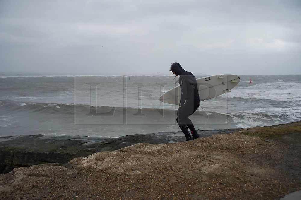 © Licensed to London News Pictures. 23/03/2013..Cleveland, England..A surfer heads into the waves as the wintery weather continues to chill the country. Cleveland on the east coast of England suffered freezing cold temperatures and strong winds that brought big seas to the coastline...Photo credit : Ian Forsyth/LNP