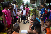 A group of Maniq children are disciplined by the head master for wearing the wrong uniform forgetting it was sports day. <br /> <br /> The Maniq of Trang province differ slightly as they were the first to give up nomadic life and became permanently settled in their own remote forest village.<br /> <br /> Evidence suggests that the Maniq, a Negrito tribe of hunters and gatherers, have inhabited the Malay Peninsula for around 25,000 years. Today a population of approximately 350 maniq remain, marooned on a forest covered mountain range in Southern Thailand. Whilst some have left their traditional life forming small villages, the majority still live the way they have for millennia, moving around the forest following food sources. <br /> <br /> Quiet and reclusive they are little known even in Thailand itself but due to rapid deforestation they are finding it harder to survive on the forest alone and are slowly being forced to move to its peripheries closer to Thai communities.