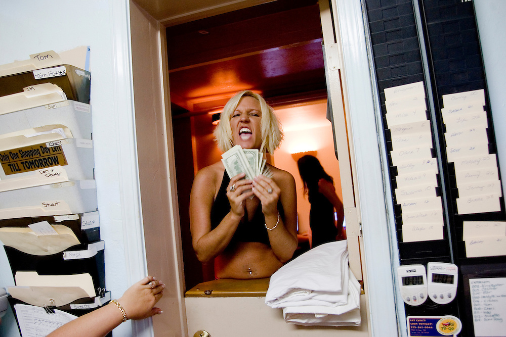"""Sex worker Kandi shows of her cash at the booking window of the Moonlite Bunny Ranch brothel in Mound House, NV on Friday, July 28, 2006...The Moonlite Bunny Ranch brothel in Mound House, Nevada - just a few miles from the state capital in Carson City - first opened in 1955. The Ranch is a legal, licensed brothel owned by Dennis Hof. It's featured in the HBO series """"Cathouse."""""""