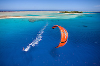 Kiteboarder cruises across a vast lagoon in Apataki, Tuamotus in French Polynesia.  I captured this shot from the top of our mast at mid day when the sun penetrates the clear water, showing the amazing colors.