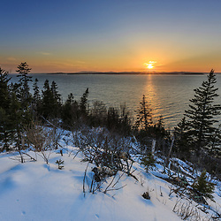 Sunset over the mouth of the Penobscot River as seen from the Witherle Woods Preserve in Castine, Maine in winter.