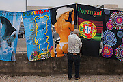 A man in a local Saturday market adjusts merchandise of sexist and Portugal-themed souvenir towels, on 19th July, in Estarreja, Portugal. A woman weaing a thong and a stetson-tyle cowboy hat shows a bare back and the others feature a map of the country with known seaside resorts and the national football emblem. (Photo by Richard Baker / In Pictures via Getty Images)