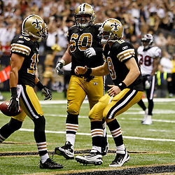September 25, 2011; New Orleans, LA, USA; New Orleans Saints quarterback Drew Brees (9) and center Brian De La Puente (60) celebrate with wide receiver Lance Moore (16) following a touchdown during the fourth quarter against the Houston Texans at the Louisiana Superdome. The Saints defeated the Texans 40-33. Mandatory Credit: Derick E. Hingle