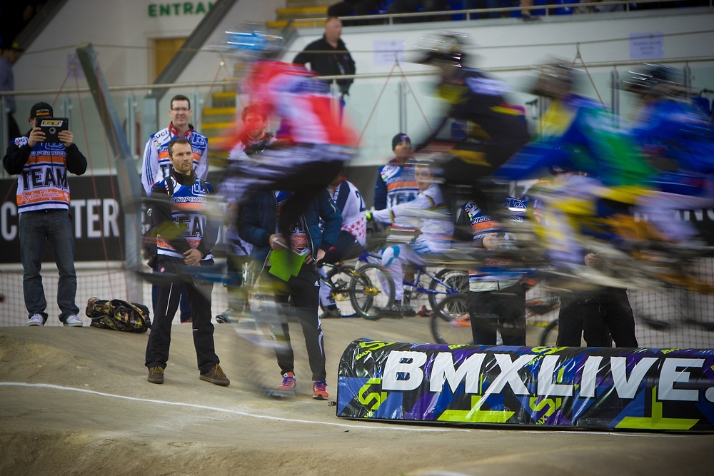 Team coaches look on as riders clear the first jump during the A practice at the UCI BMX Supercross World Cup in Manchester, UK