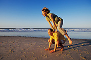 Couple playing leapfrog on the beach, Queensland, N. Stradbroke Island, Australia people ****Model Release available