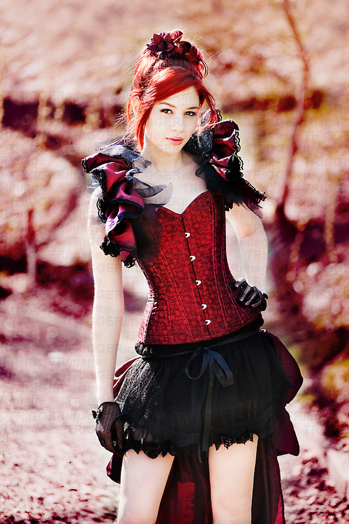 Redhead female dressed in victorian style corset