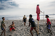 BALI, INDONESIA; APRIL 16, 2015: Balinese youngsters play beach volleyball at Batu Belig beach, Bali, Indonesia on Thursday, April 16, 2015.