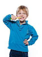 studio portrait of a beautiful cute caucasian blond boy with a toothbrush
