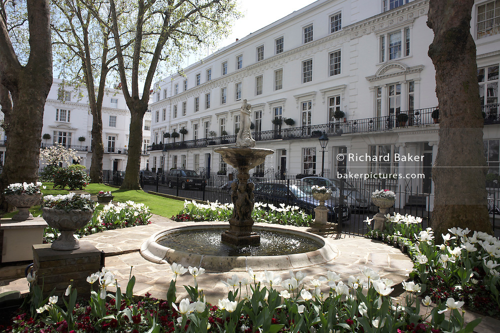 Identical white-painted properties and ornamental fountain with central garden area in exclusive Wellington Square SW1