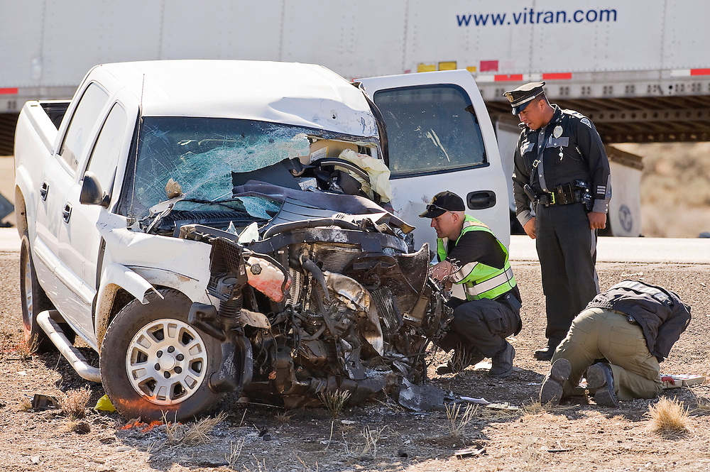 031312       Brian Leddy.New Mexico State Police officers work on a truck that was apparently involved in a suicide. The driver was involved in a domestic dispute and was being chased by police when he crossed the centerline on Interstate 40, crashing head-on into a semi.
