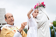 Father John Lombardi stands by as Abigail Golden, 8,places a crown of flowers atop a statue of Mary during a May Crowning May 6 at St. Peter, Hancock.